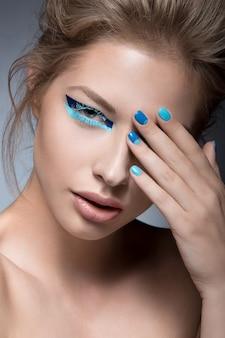 Mooi meisje met heldere creatieve maniermake-up en blauwe nagellak.