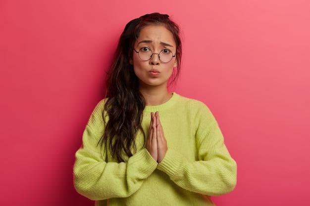 Mooi meisje met hulpeloze uitdrukking, vraagt om hulp, smeekt om vergeving met een zielig gezicht, houdt de handpalmen tegen elkaar gedrukt, maakt een gebedgebaar Gratis Foto