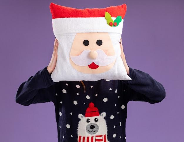 Mooi meisje met kerst trui en hoed met bril bedekt gezicht met kerst kussen geïsoleerd op paarse achtergrond