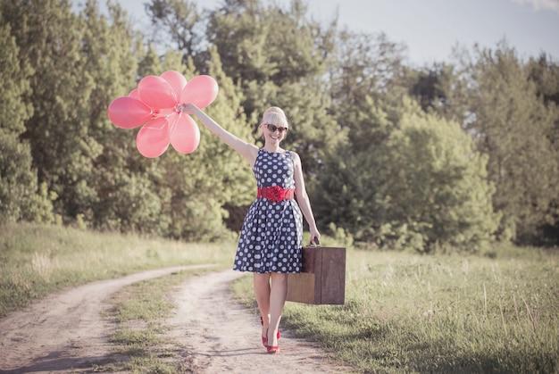 Mooi meisje met koffer en rode ballonnen op platteland