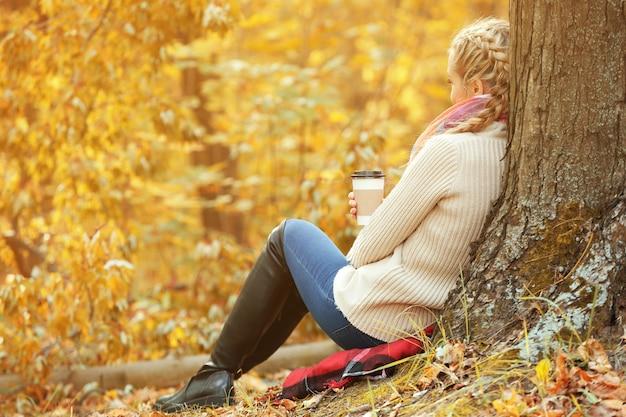 Mooi meisje met koffie in de herfstpark