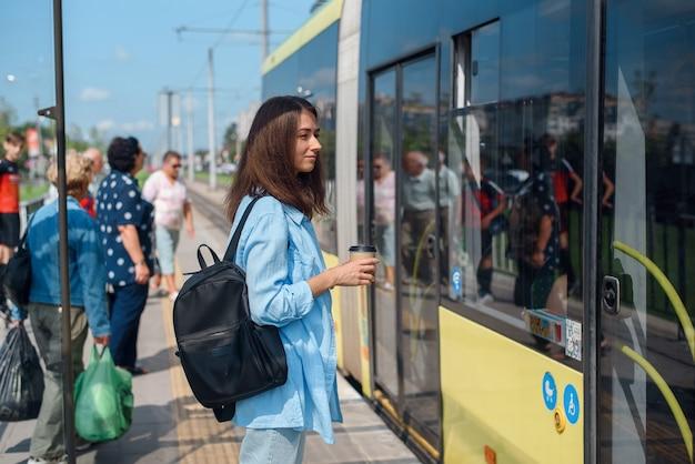 Mooi meisje met kopje koffie komt in de moderne tram op het station.