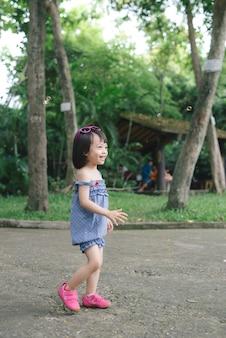 Mooi meisje met kort haar, heeft een vrolijk lachend gezicht, mooie ogen, kort haar, zeepbellen spelen, gekleed, kinderportret. creatief concept.