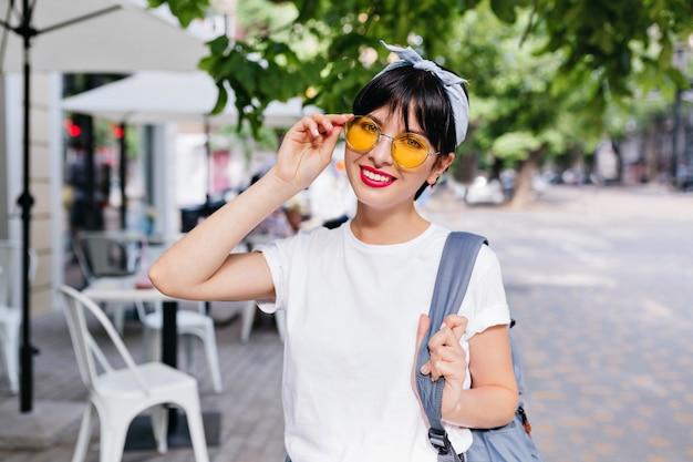 Mooi meisje met kort zwart haar glimlachend en blauwe rugzak op een schouder te houden terwijl poseren op straat in de ochtend