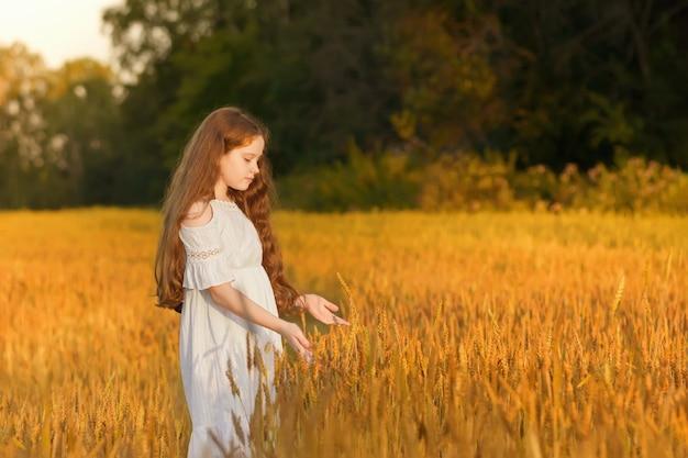 Mooi meisje met krullend haar op tarwe of rogge veld.