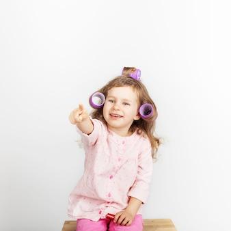 Mooi meisje met krulspelden op haar hoofd camera kijken en plezier thuis