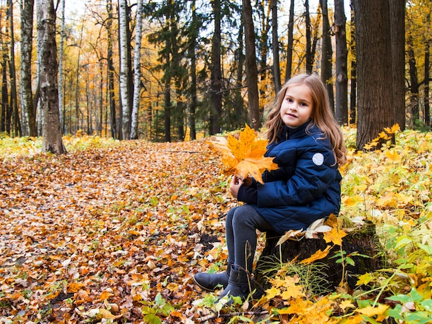 Mooi meisje met lang blond haar in het herfstpark. bruinogig meisje met gouden lokken op een achtergrond van gele herfstbladeren