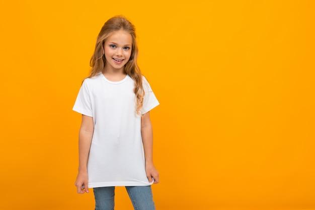 Mooi meisje met lang blond haar op een gele achtergrond in een wit t-shirt zonder inscripties
