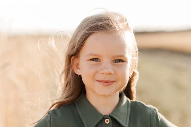 Mooi meisje met lang haar dat op een zonnige dag door een tarweveld loopt. buiten portret. kinderen ontspannen