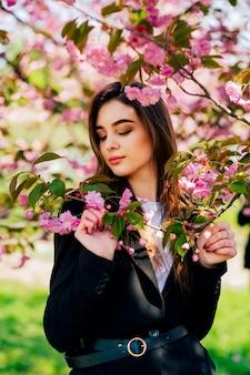 Mooi meisje met lang haar geniet van de schoonheid van de lenteaard in de buurt van de bloeiende sakuraboom.