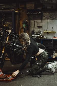 Mooi meisje met lang haar in de garage die een motorfiets herstelt