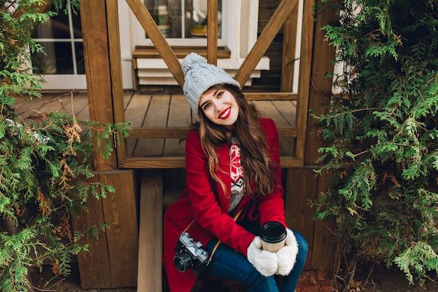 Mooi meisje met lang haar in een rode jas, zittend op houten trappen tussen groene takken buiten. ze houdt koffie in witte handschoenen en lacht. uitzicht van boven.