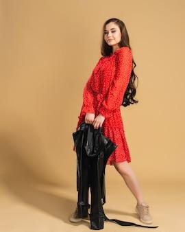Mooi meisje met lang haar in een rode jurk met noppen poseren met een zwart leren jasje in haar handen op een pastel oranje.