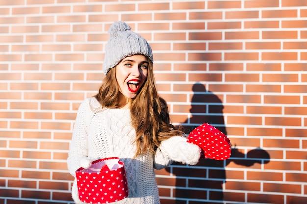 Mooi meisje met lang haar in gebreide muts en handschoenen met open aanwezig op muur buiten. ze ziet er verbaasd uit.