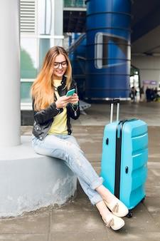 Mooi meisje met lang haar in glazen zit buiten op de luchthaven. ze draagt een gele trui, een zwarte jas en een spijkerbroek. ze heeft een koffer in de buurt en is aan het typen op de telefoon.