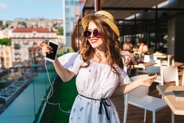 Mooi meisje met lang haar in zonnebril luistert naar muziek via een koptelefoon op het terras. ze draagt een witte jurk met blote schouders, rode lippenstift en hoed. ze is aan het dansen.