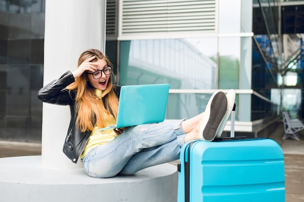 Mooi meisje met lang haar in zwarte bril zit buiten op de luchthaven. ze draagt een spijkerbroek, een zwart jasje, gele schoenen. ze legde haar benen op de koffer en sprak op de laptop. ze kijkt verbaasd.