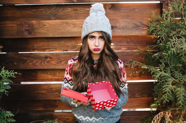Mooi meisje met lang haar met lege kerstdoos op houten. ze draagt warme winterkleren, ziet er ontevreden uit.
