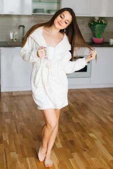 Mooi meisje met lang haar staan in de keuken en drinkt koffie.