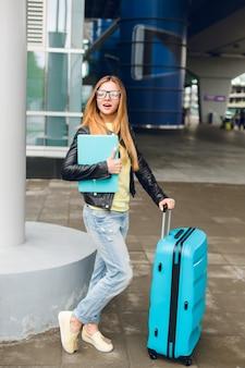 Mooi meisje met lang haar staat met koffer buiten op de luchthaven. ze draagt een zwarte jas met een spijkerbroek en houdt een laptop vast. ze kijkt verbaasd.