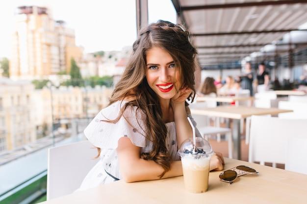 Mooi meisje met lang haar zit aan tafel op het terras in café. ze draagt een witte jurk met blote schouders en rode lippenstift. ze lacht naar de camera.