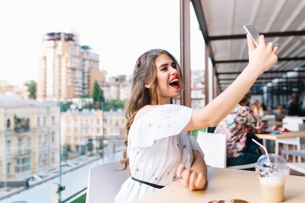 Mooi meisje met lang haar zit aan tafel op het terras in café. ze draagt een witte jurk met blote schouders en rode lippenstift. ze maakt een selfie-portret met telefoon.,