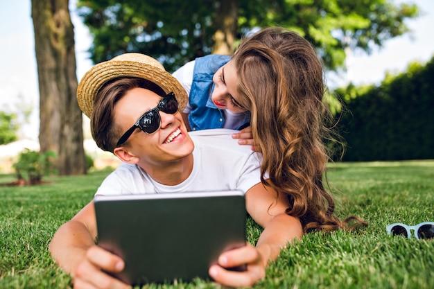 Mooi meisje met lang krullend haar en rode lippen ligt op achterkant knappe jongen in zonnebril op gras in zomer park. man houdt tablet vast, meisje lacht hem toe.