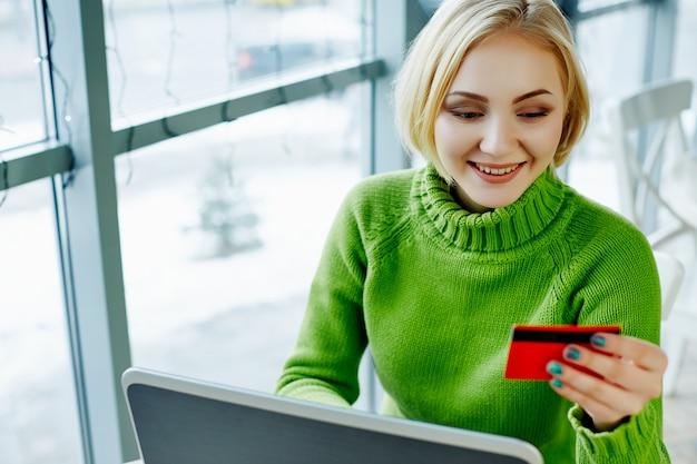 Mooi meisje met licht haar dragen groene trui zitten in café met laptop en creditcard, portret, freelance concept, online winkelen.