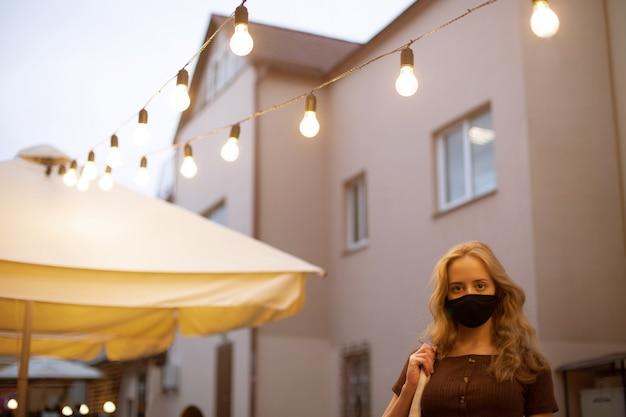 Mooi meisje met licht haar in een zwart medisch masker dat in de avondstad loopt