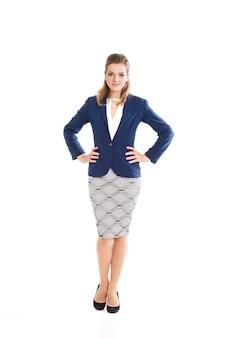 Mooi meisje met lichtbruin haar in een stijlvolle jurk, rok strak lichtblauw jasje en zwarte schoenen met hoge hakken, kantoorkleding