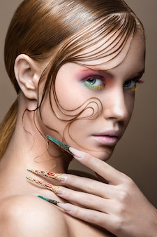 Mooi meisje met lichte fashion make-up, creatief kapsel, lange nagels.