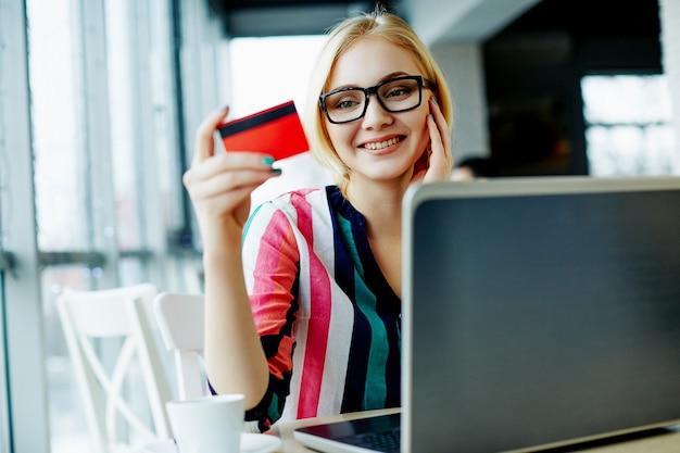 Mooi meisje met lichte haren dragen kleurrijke shirt en bril zitten in café met laptop en creditcard, freelance concept, online winkelen, glimlachend.
