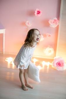 Mooi meisje met lichte kussens in een gezellige kamer
