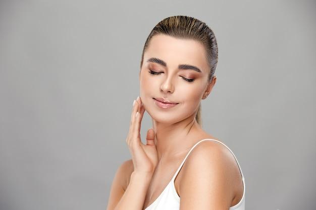 Mooi meisje met lichte make-up glimlachend met haar ogen dicht en haar wang op grijze muur, gezond en schoonheidsconcept aan te raken
