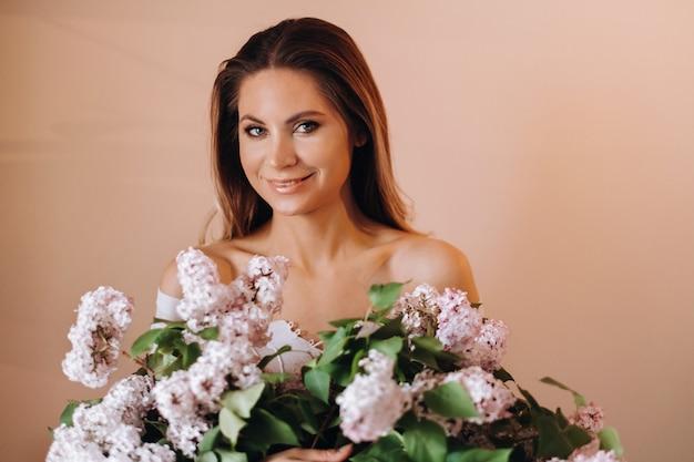 Mooi meisje met lila bloemen in haar handen. een meisje met lila bloemen in de lente thuis. een meisje met lang haar en lila in haar handen.