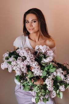 Mooi meisje met lila bloemen in haar handen