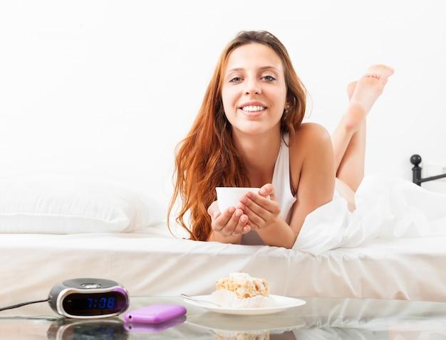 Mooi meisje met mok koffie in haar bed