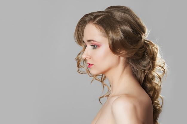 Mooi meisje met natuurlijke make-up en krullend haar dat zich in profiel bevindt