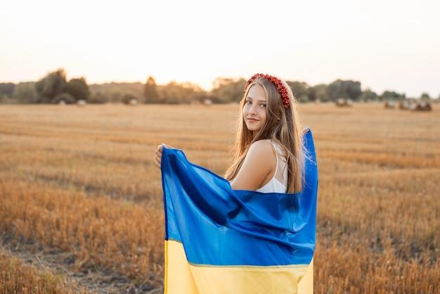 Mooi meisje met oekraïense vlag op een plattelandsgebied tegen ondergaande zon