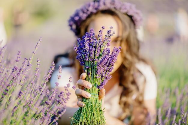 Mooi meisje met paars violet lavendelboeket op het lavendelveld