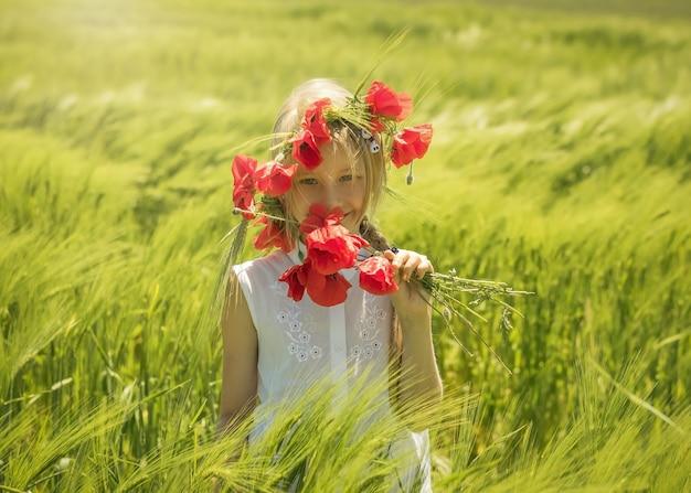 Mooi meisje met papavers op een groen veld.