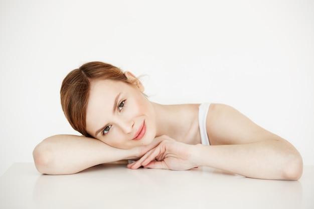 Mooi meisje met perfecte schone huid glimlachen zittend aan tafel. beauty spa en cosmetologie.