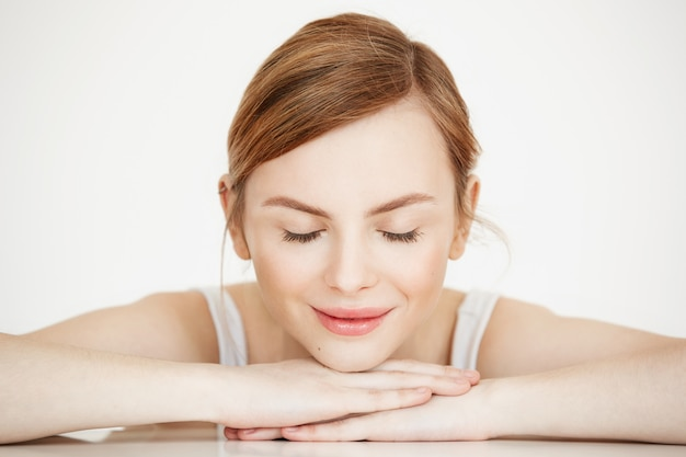 Mooi meisje met perfecte schone huid lachend met gesloten ogen aan tafel zitten. beauty spa en cosmetologie.