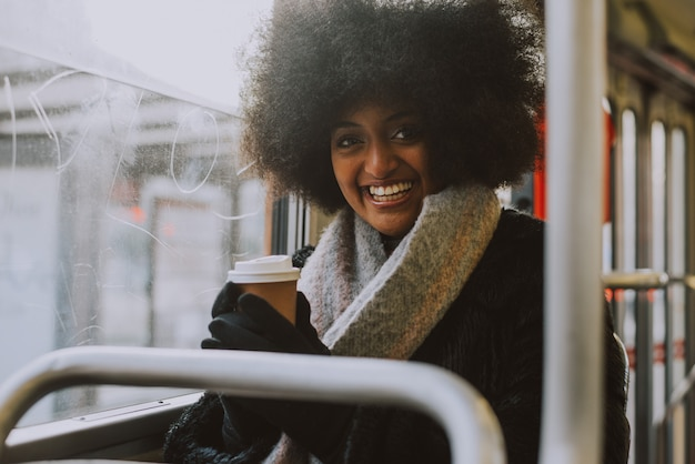 Mooi meisje met portretten van het afrokapsel in het openbaar vervoer