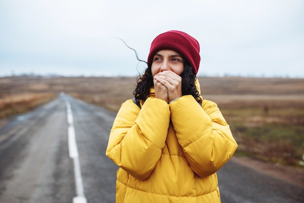 Mooi meisje met rode hoed en gele jas verwarmt haar handen met haar adem op de eenzame weg.