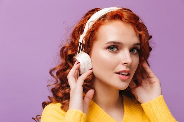 Mooi meisje met rode krullen kijkt naar voren en luistert naar liedjes in een koptelefoon op de paarse muur