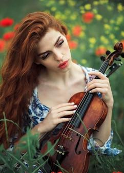 Mooi meisje met rood haar en de blauwe viool van de kledingsholding op aardgebied van bloemen.