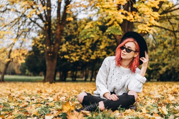 Mooi meisje met rood haar en hoed het ontspannen in het park, de herfsttijd.