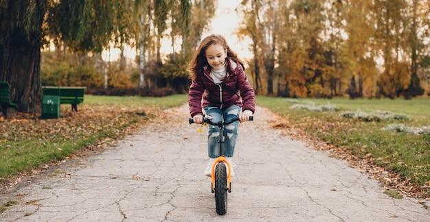 Mooi meisje met rood haar rijdt op de fiets in het park tijdens een herfstwandeling