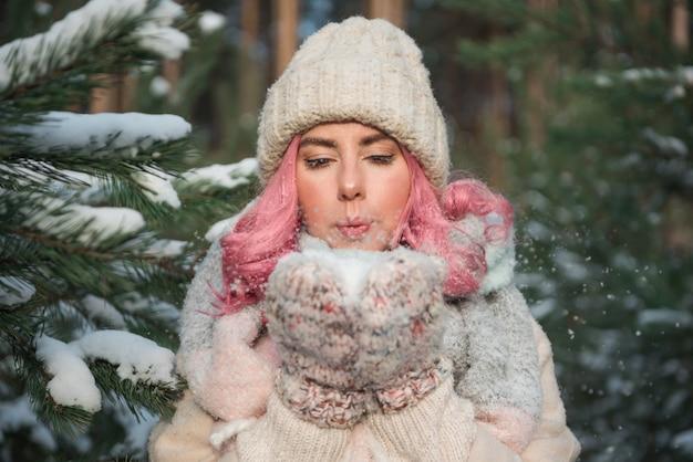 Mooi meisje met roze haar dat sneeuw in handen blaast